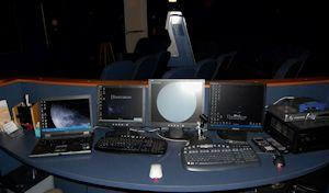Planetariums control console, four different monitors on a desk with 3 different keyboards help run the show